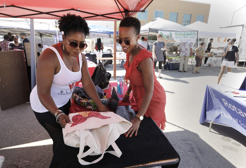 Dree Berry, left, admires the butterfly on the canvas bag of Jasmine L. Sadler, right. Berry is with San Diego Black Professionals and Sadler is with Jas:Maven and The STEAM Collaborative. Both attended the Summer Y.E.S. Fest held by Young Black&'N Business.