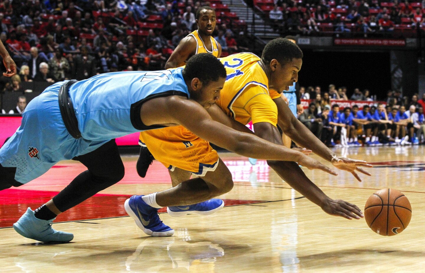 The Aztecs' Matt Mitchell, left, and McNeese State's Stephen Ugochukwu dive for a loose ball during the second half.