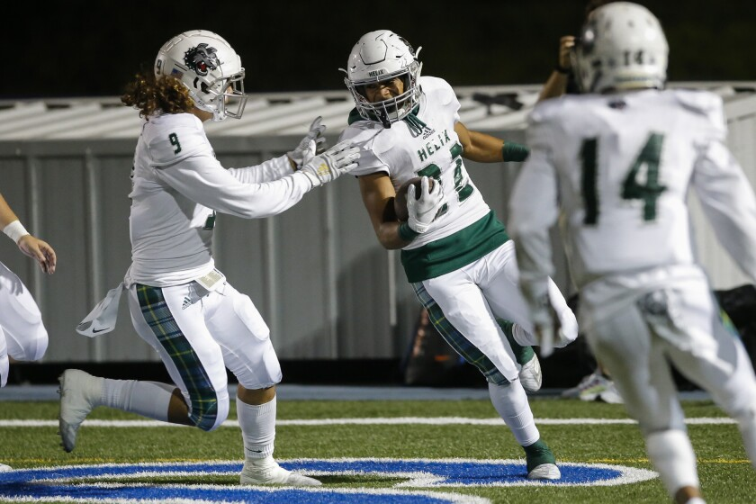 Helix linebacker Jeremiah Fletcher (22) celebrates with teammates after picking up a Saints fumble last month. The Highlanders are No. 1 in MaxPreps' customized rankings for the San Diego Section.