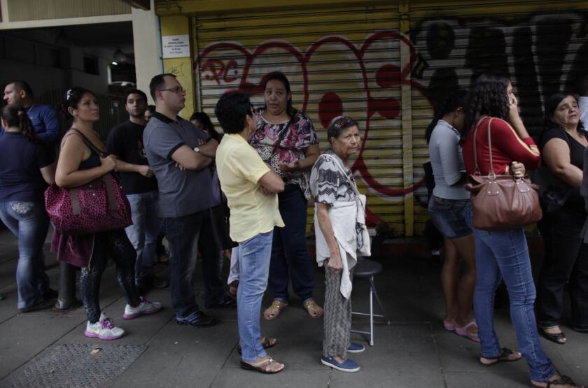 Shoppers stand in line as they wait to enter an appliance store in Caracas, Venezuela, on Monday. President Nicolas Maduro seized control of a nationwide chain of appliance stores Friday seeking to battle inflation and shortages.