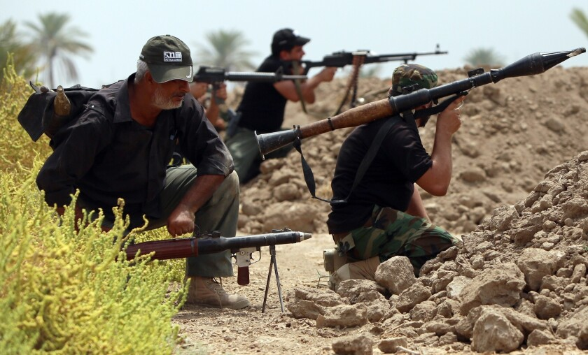 Shiite Muslim fighters with the Peace Brigade, a militia formed by Iraqi cleric Muqtada Sadr, hold a position on the Jarf Sakhr front line souuthwest of Bahgdad on Monday.