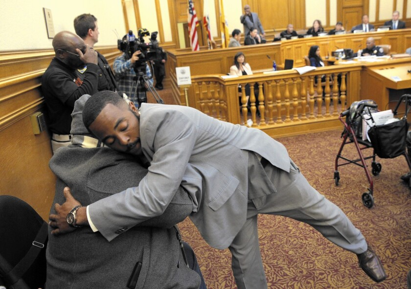 Will Hambrick hugs Robert Harris after giving his public comment at the San Francisco Police Commission meeting. The fate of several police officers involved in racist and homophobic text messaging was under consideration.