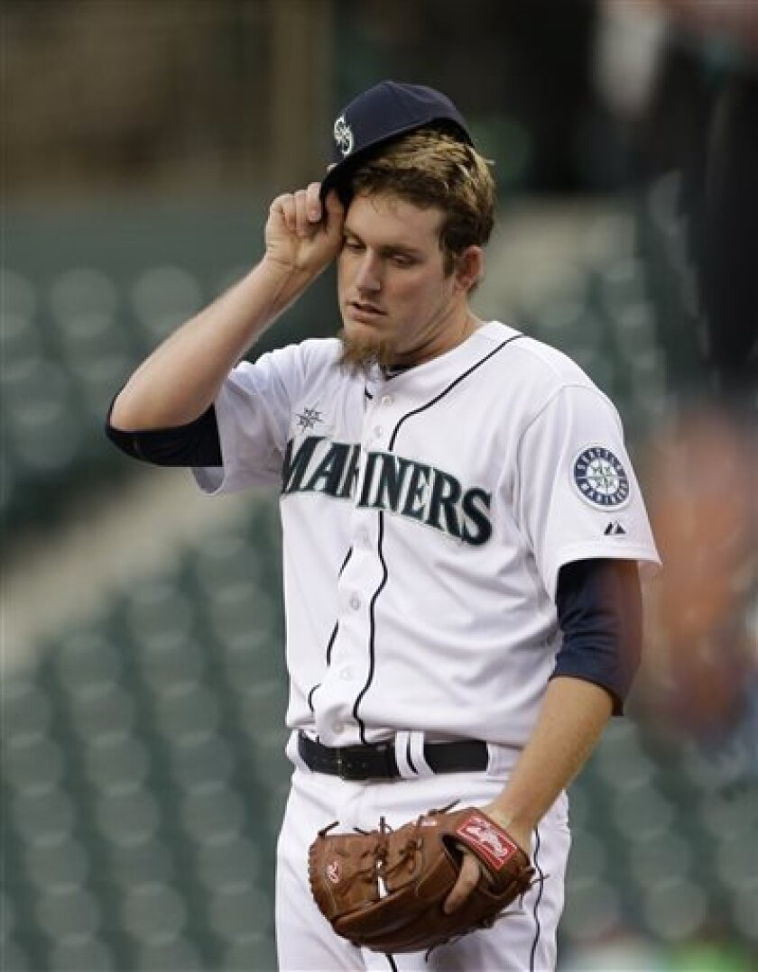 Seattle Mariners starting pitcher Brandon Maurer adjusts his cap after giving up a run to the Baltimore Orioles in the first inning of a baseball game Tuesday, April 30, 2013, in Seattle. (AP Photo/Elaine Thompson)