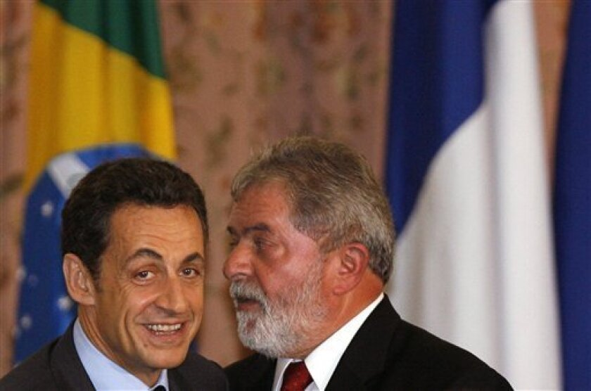 French President Nicolas Sarkozy, left, listens to Brazil's President Luiz Inacio Lula da Silva after signing bilateral agreements in Rio de Janeiro, Tuesday, Dec. 23, 2008. Sarkozy is on a two-day official visit to Brazil. (AP Photo/Andre Mourao)