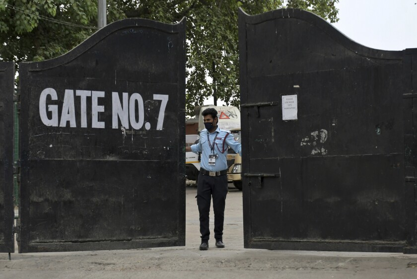 A security guard closes the gate of Arun Jaitley Stadium, one of the six venues of Indian Premier League 2021, in New Delhi, India, Tuesday, May 4, 2021. The Indian Premier League was suspended indefinitely on Tuesday after players or staff at three clubs tested positive for COVID-19 as nationwide infections surged. (AP Photo/Ishant Chauhan)