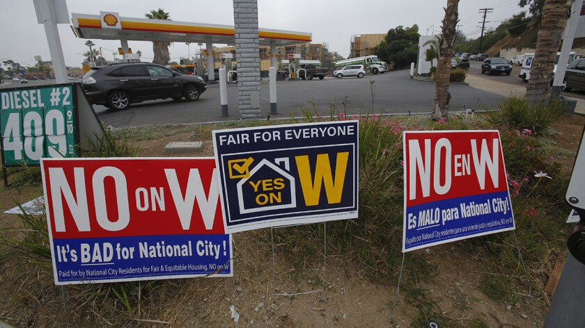 Election signs supporting and opposing Measure W, a rent control measure on the November ballot, on the corner of Palm Avenue and Plaza Blvd where a 77-unit apartment building is under construction.