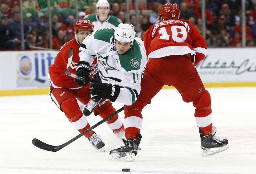 Dallas Stars left wing Jamie Benn (14) is checked by Detroit Red Wings center Joakim Andersson (18) in the third period of an NHL hockey game, Sunday, Nov. 8, 2015 in Detroit. (AP Photo/Paul Sancya)