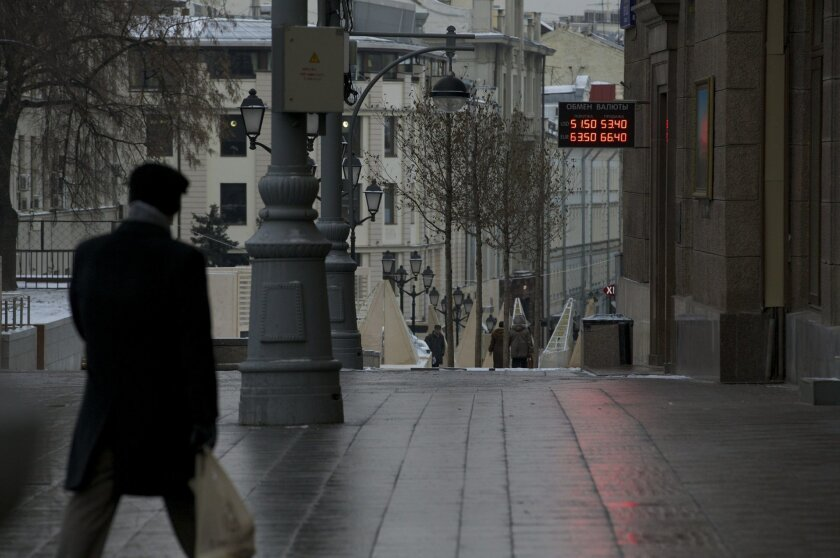 A man walks at an empty street in downtown Moscow, Russia, Tuesday, Dec. 2, 2014. The Russian government has for the first time acknowledged that the country will fall into recession next year, battered by the plunge in the price of its oil exports. (AP Photo/Ivan Sekretarev)