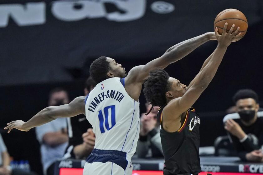 Collin Sexton, derecha, de los Cavaliers de Cleveland, trata de encestar en contra de Dorian Finney-Smith, de los Mavericks de Dallas, en duelo del domingo 9 de mayo de 2021, en Cleveland. (AP Foto/Tony Dejak)