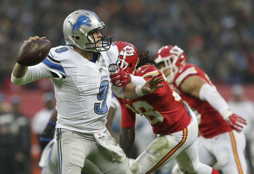 Detroit Lions quarterback Matthew Stafford (9), left, is grabbed by Kansas City Chiefs strong safety Ron Parker (38) during the NFL football game between Detroit Lions and Kansas City Chiefs Wembley Stadium in London,  Sunday, Nov. 1, 2015. (AP Photo/Tim Ireland)
