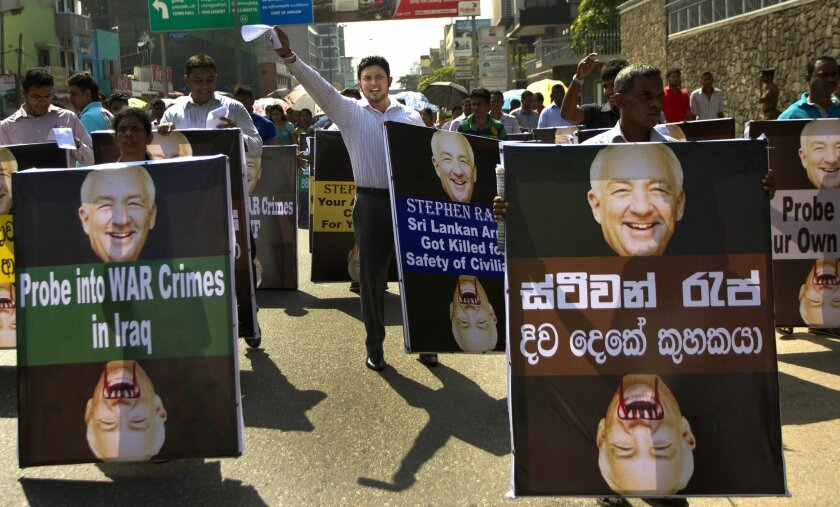 """Members of Sri Lanka's pro-government political party, National Freedom Front, hold placards carrying portraits of Stephen J. Rapp, an ambassador-at-large in the Office of Global Criminal Justice during a protest outside the U.S. Embassy in Colombo, Sri Lanka, Thursday, Jan. 9, 2014. Rapp is currently visiting Sri Lanka meeting ethnic Tamil politicians and religious leaders. He is scheduled to meet government leaders before leaving the island on Saturday. Placard written in Sinhalese reads """" Stephen Rapp Double Tongued Hypocrite."""" (AP Photo/Eranga Jayawardena)"""