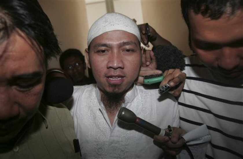 Alleged Islamic militant Amir Abdillah, center, is escorted by plain-clothed police officers after his first trial at South Jakarta District Court in Jakarta, Indonesia, Wednesday, Feb. 10, 2010. Abdillah went on trial Wednesday on charges of harboring terrorists behind twin suicide hotel bombings in the Indonesian capital that killed seven and wounded more than 50 last year. (AP Photo/Tatan Syuflana)