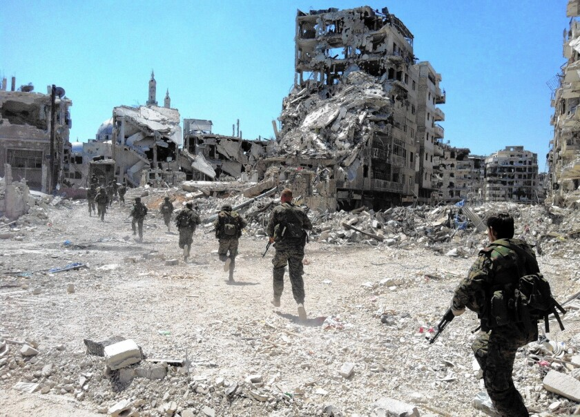 A photo from July 2013 shows Syrian government forces patrolling in the central city of Homs. Essential to the government's resurgence has been its well-armed military. Long trained for a traditional land war with Israel, it has become increasingly adept at fighting an insurgency.