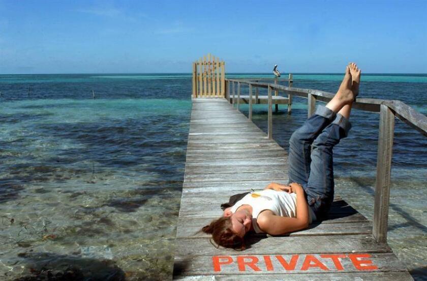 Rebeca Hewith, de 24 años, descansa sobre el muelle de madera en los Cayos de la costa de Belice. La industria turística en el Caribe representa dos tercios del negocio del turismo en América Latina. EFE/Archivo