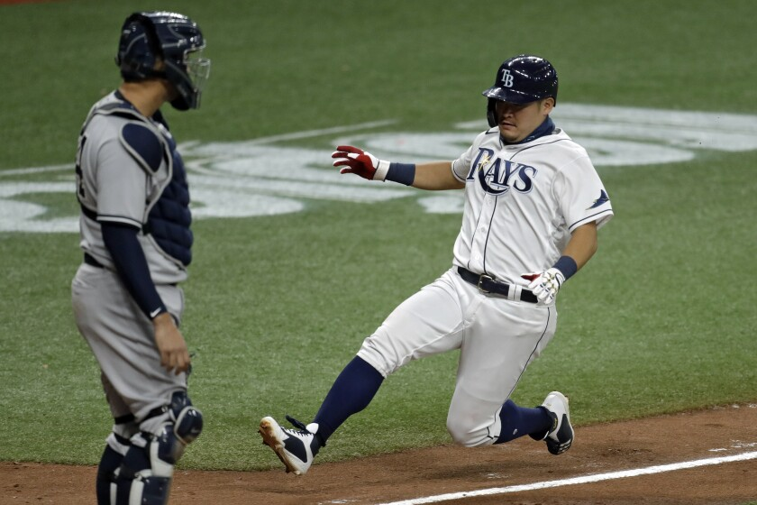 Tampa Bay Rays' Yoshi Tsutsugo, of Japan, right, scores in front of New York Yankees catcher Gary Sanchez on a sacrifice fly by Michael Perez off Yankees pitcher Adam Ottavino during the eighth inning of a baseball game Friday, Aug. 7, 2020, in St. Petersburg, Fla. (AP Photo/Chris O'Meara)