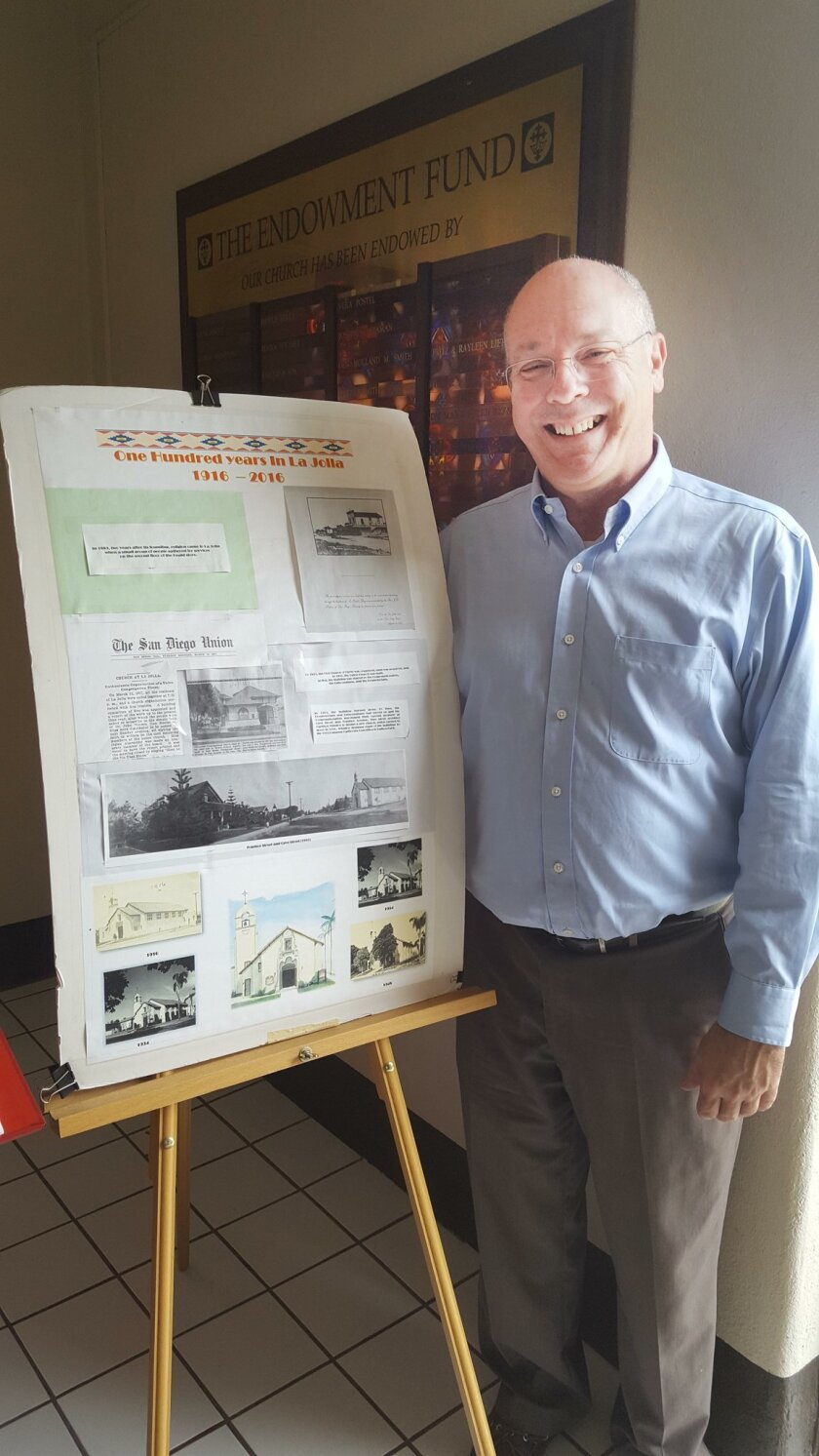 Pastor Sam Greening poses with an information board at the church entrance, which shows some highlights of the last 100 years.