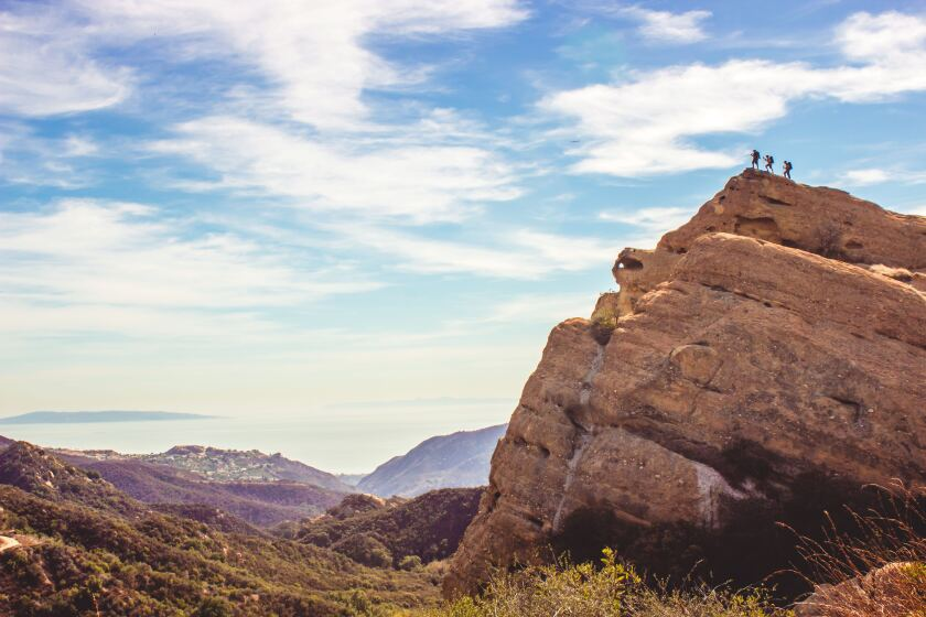 Hikers stand atop Eagle Rock in Topanga State Park, a spot to see along the 67-mile Backbone Trail in the Santa Monica Mountains.