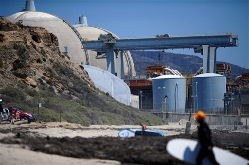 FILE - In this July 19, 2012 file photo, surfers walk along a beach nearby the San Onofre Nuclear Power Plant in San Onofre, Calif. U.S. Sen. Barbara Boxer wants the Justice Department to investigate if California utility executives deceived federal regulators about an equipment swap at the San Ono