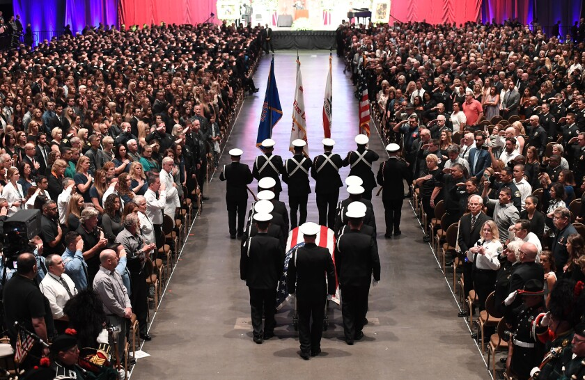 The casket of Lone Beach firefighter Capt. Dave Rosa enters the Long Beach Convention Center during his memorial service Tuesday.
