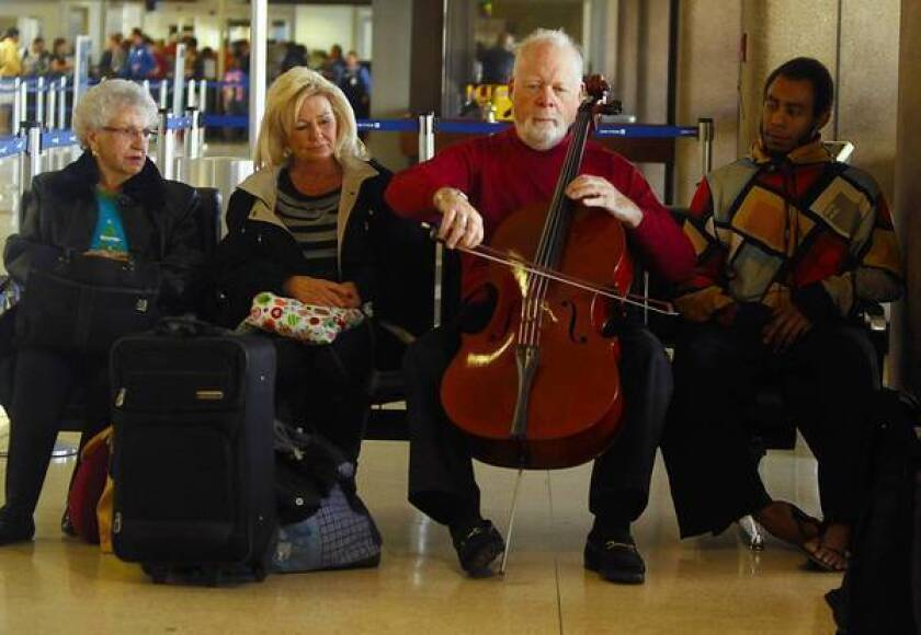 Musician Lynn Harrell often takes his cello out of the case and plays a little in Los Angeles International Airport on Dec. 21, 2012. Harrell travels with his expensive cello in and out of airports around the world.
