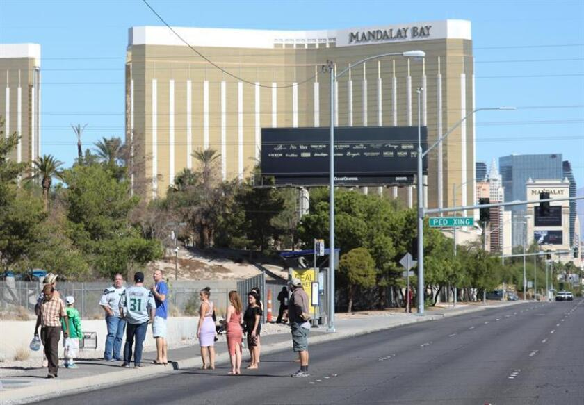Turistas caminan cerca al lugar donde ocurrió un tiroteo mientras se llevaba a cabo un festival de música country, en Las Vegas, Nevada. EFE/Archivo