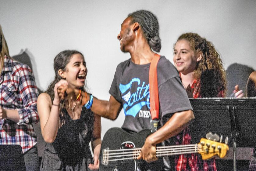 "Lead singer Arthur ""Trey"" Carlisle is congratulated by Sally Sayed after the group sang ""Rehumanize"" at the Sept. 11 Music in Common event in Laguna Beach. Valerie Klein is at right."