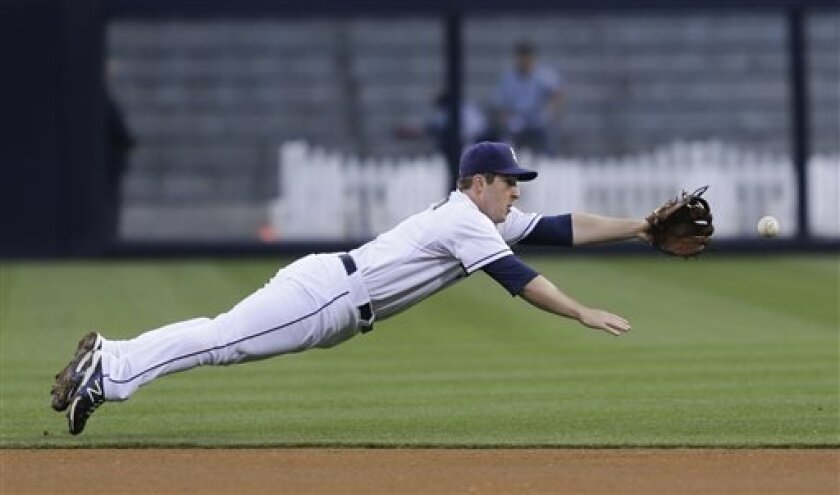 San Diego Padres second baseman Jedd Gyorko makes a diving attempt but can't reach a single by Miami Marlins' Placido Polanco during the first inning of a baseball game in San Diego, Tuesday, May 7, 2013. (AP photo/Lenny Ignelzi)