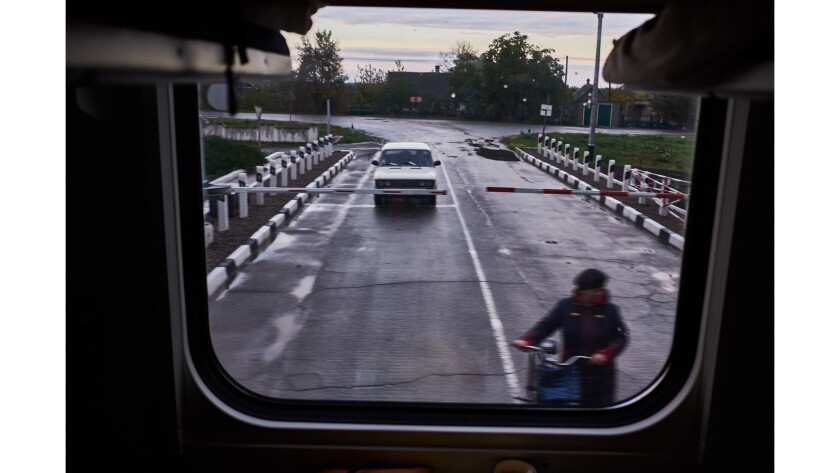 A paseenger car waits at a railroad crossing for a Ukrainian train to pass on its way to the Crimean
