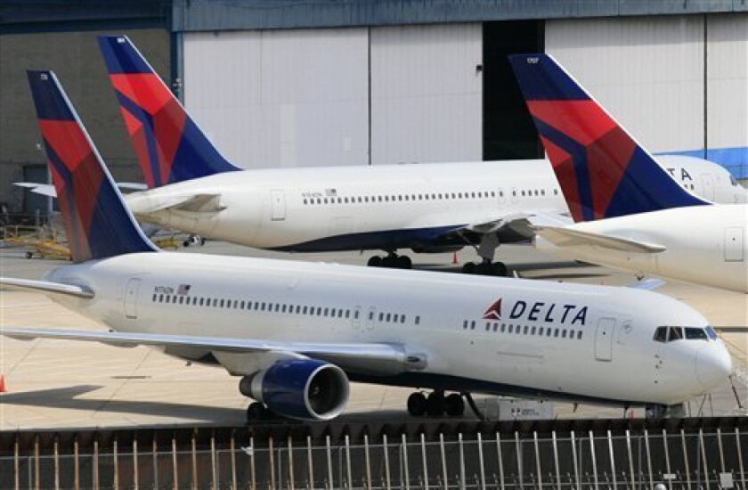 FILE - In this April 20, 2010 file photo, Delta Air Lines jets are parked at John F. Kennedy International Airport, in New York. Delta Air Lines Inc. said Tuesday, April 26, 2011, raising fares should allow it to make up for the higher fuel prices that drove a $318 million loss in the first quarter