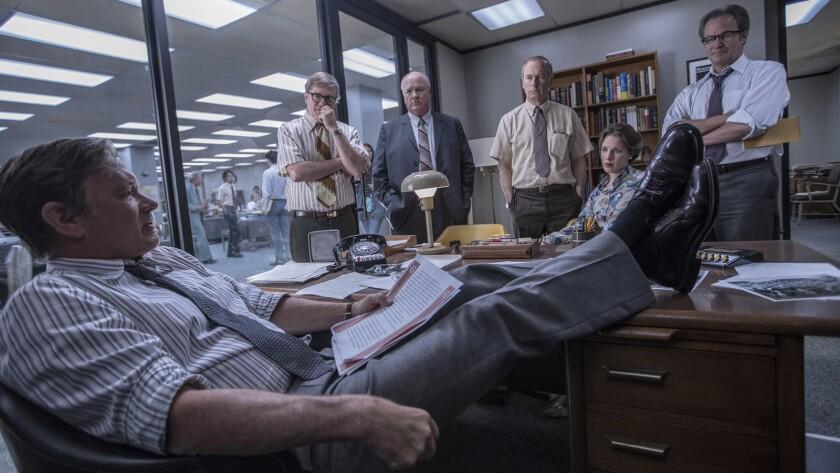 "Tom Hanks, from, left, David Cross, John Rue, Bob Odenkirk, Jessie Mueller and Philip Casnoff in the movie ""The Post."""