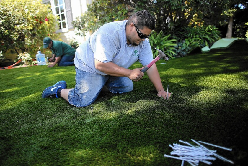 Juan Martinez installs a section of articficial lawn at a home in Burlingame. The MWD offers rebates for artificial turf, but some cities ban it.