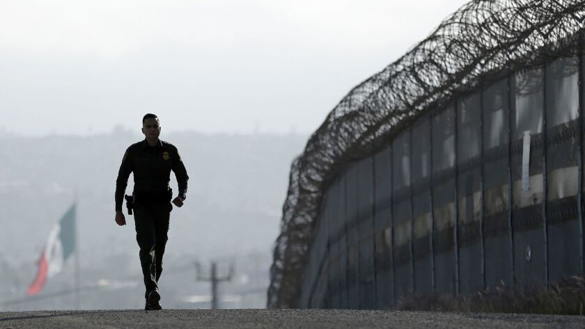 A Border Patrol agent near the secondary fence separating Tijuana, background, and San Diego.