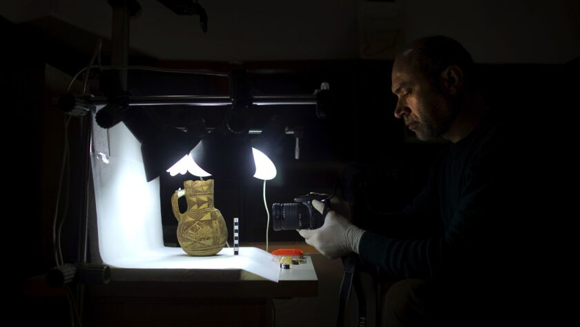 An archaeologist at the National Museum in Damascus examines an artifact rescued from southern Syria. The appetite for Syria's artifacts has created an opening for counterfeits.