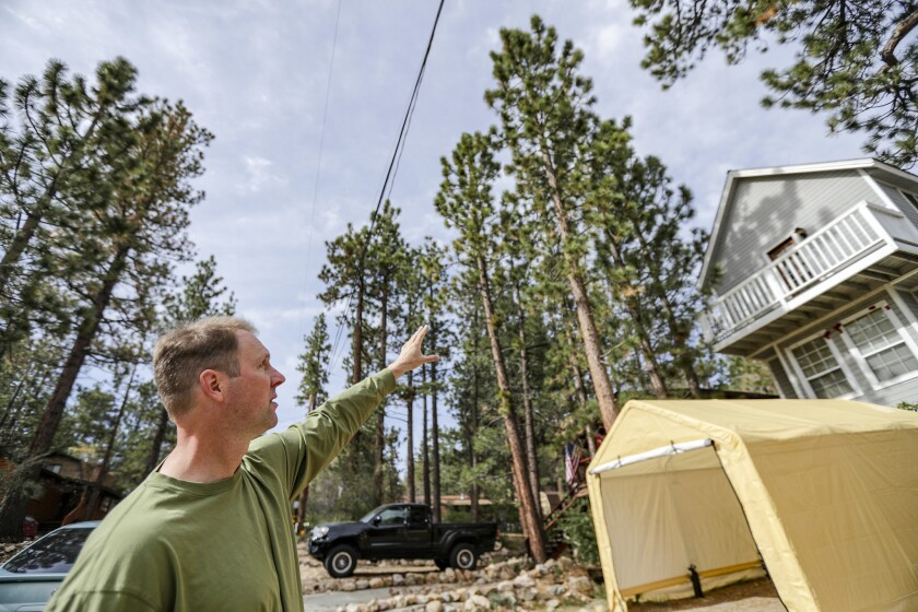 Chad Hanson, executive director and research ecologist at John Muir Project of Earth Island Institute, points to extreme fire danger because of overgrown grasses and trees very close to and hanging over structures in the residential community of Sugarloaf near Big Bear.