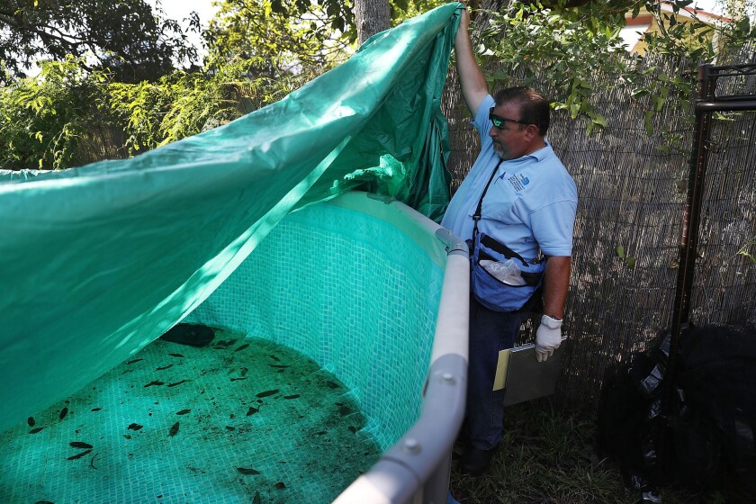 Robert Muxo, a Miami-Dade County mosquito control inspector, inspects a property for mosquitoes or breeding areas in the Wynwood neighborhood Saturday as the county fights to control the Zika virus outbreak.