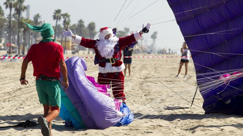 Santa Claus comes in for a landing in Huntington Beach near Pacific City on Saturday, November 18.
