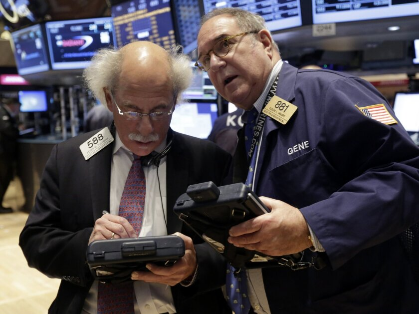 FILE - In this Tuesday, Nov. 19, 2013, file photo, traders Peter Tuchman, left, and Eugene Mauro confer on the floor of the New York Stock Exchange. The Dow's first close above 16,000 pushed most world stocks higher Friday Nov. 22, 2013 but gains were kept in check by worries the Federal Reserve wi