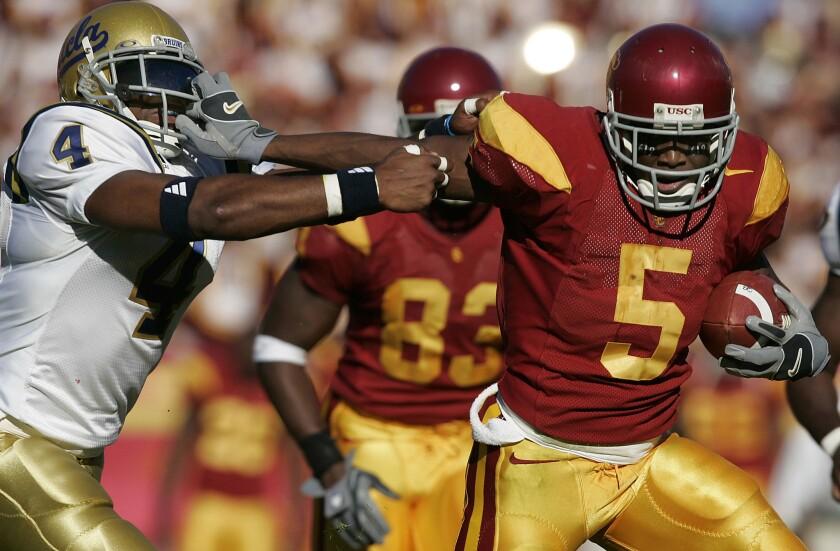 USC's Reggie Bush stiff arms UCLA's Jarrad Page in 2005.