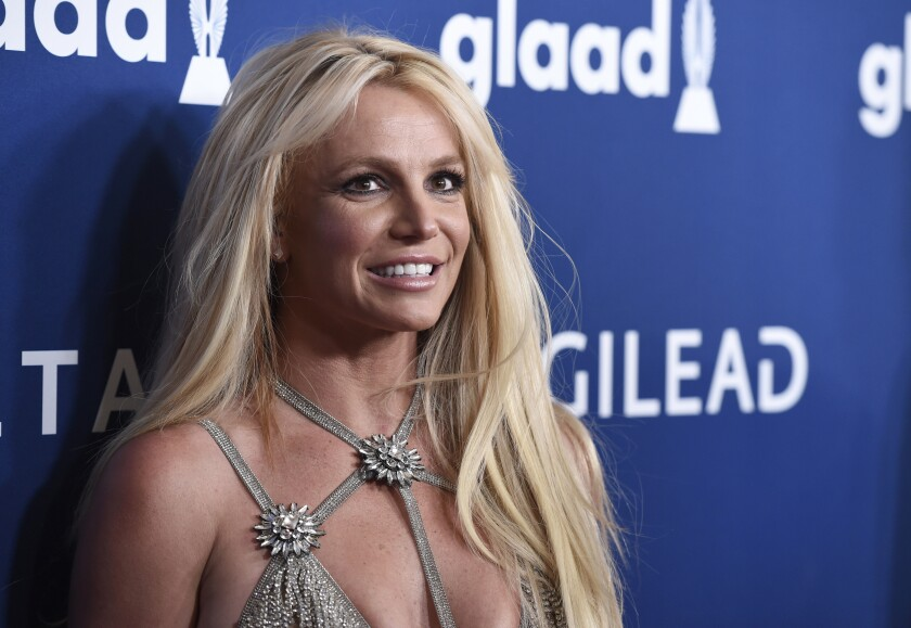 Britney Spears pictured from chest up, arriving at annual GLAAD Media Awards in 2018, smiling at the cameras