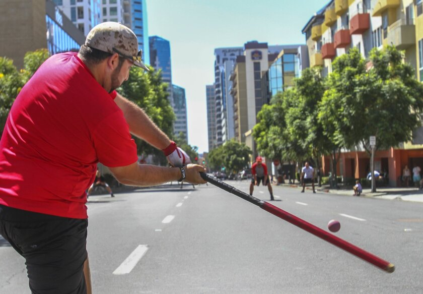 Manny Martinez of the San Diego Street Rookies hits a ball south on Columbia Street in San Diego Sunday during the Labor Day stickball tournament. It takes only one strike to be out.