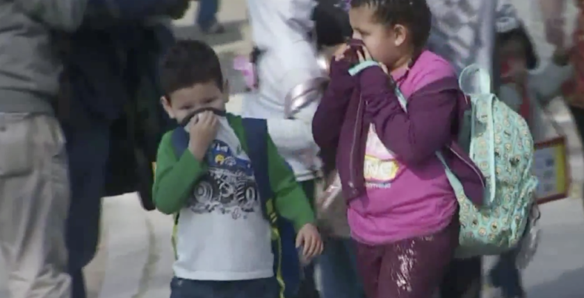 Children cover their noses after a jetliner dumped fuel on their school campus in Cudahy while making an emergency landing at Los Angeles International Airport.