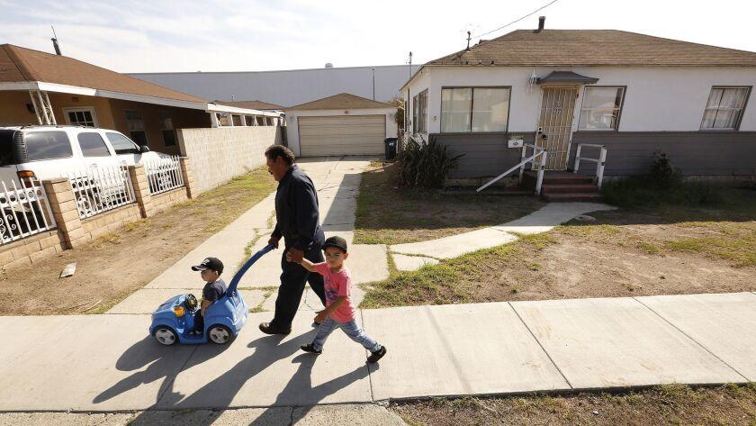 HAWTHORNE, CA - OCTOBER 22, 2018 - Antonio Salcido walks with his two grandchildren Nathan and Alber