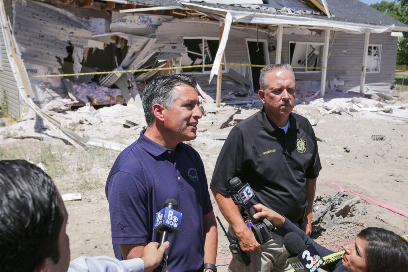 Nevada Gov. Brian Sandoval, left, speaks to the media and community members with Lincoln County Sheriff Kerry Lee on Friday, July 15, 2016, at a destroyed house in Panaca, Nev., about a Wednesday night bombing. (Brett Le Blanc/Las Vegas Review-Journal via AP)