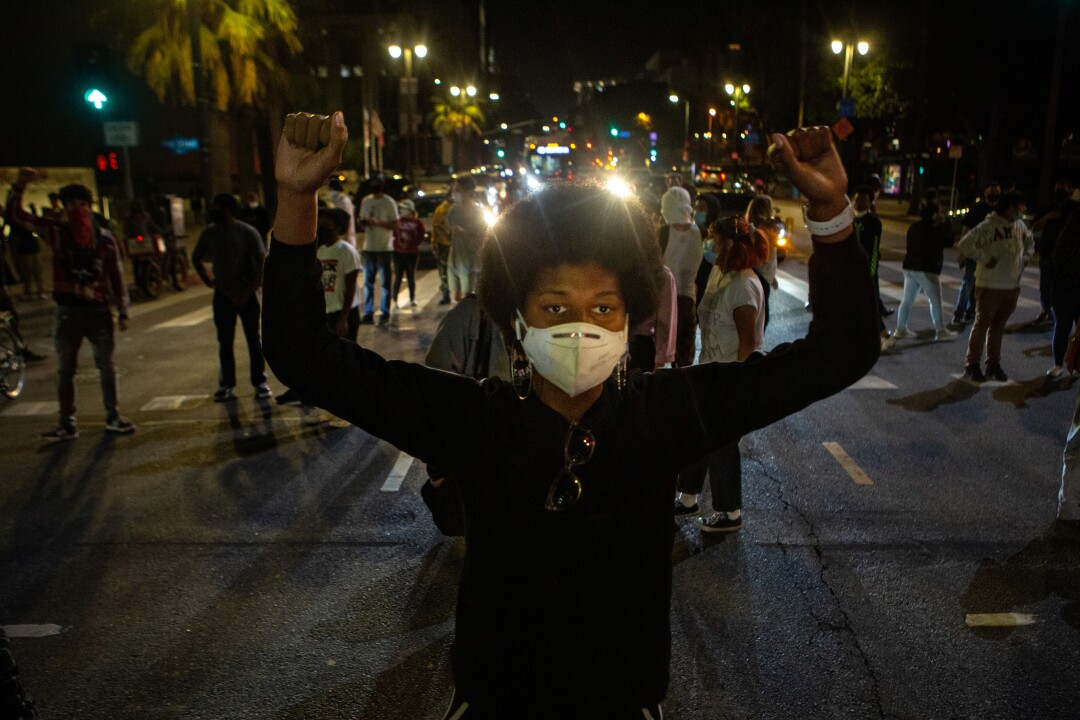 Keni James  of Los Angeles helps block a road in downtown L.A. during a protest over the killing of George Floyd by Minneapolis police.