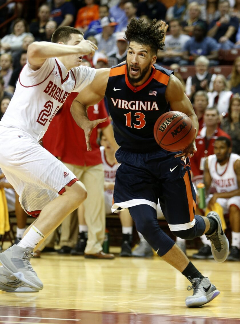 Virginia's Anthony Gill, right, drives against Bradley's Scottie James during the first half of an NCAA college basketball game at the Charleston Classic at TD Arena, Thursday Nov. 19, 2015, in Charleston, S.C. (AP Photo/Mic Smith)