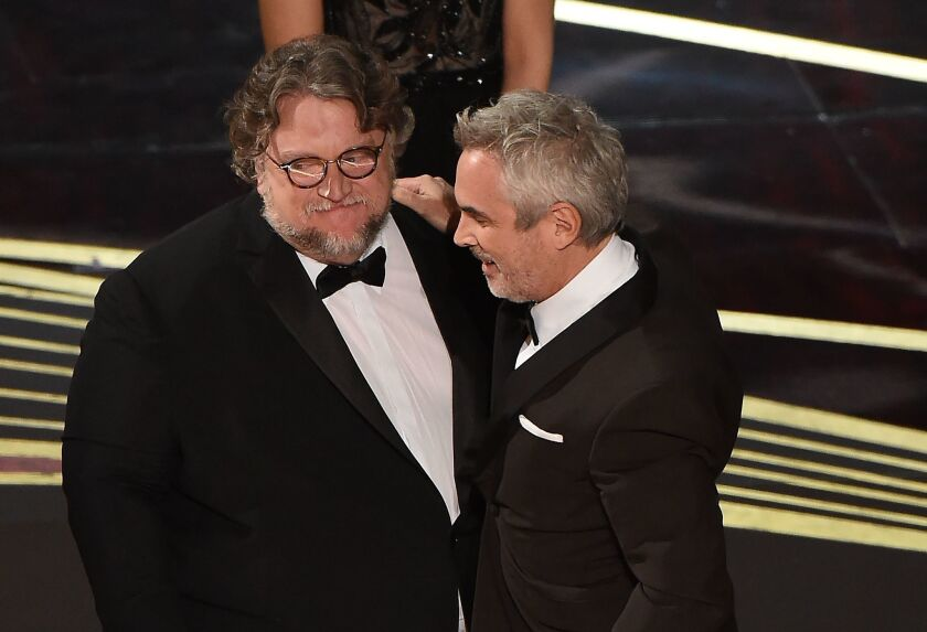 Alfonso Cuarón acepta su premio como Mejor Director de manos de su compatriota Guillermo Del Toro en el Dolby Theatre de Hollywood, California.