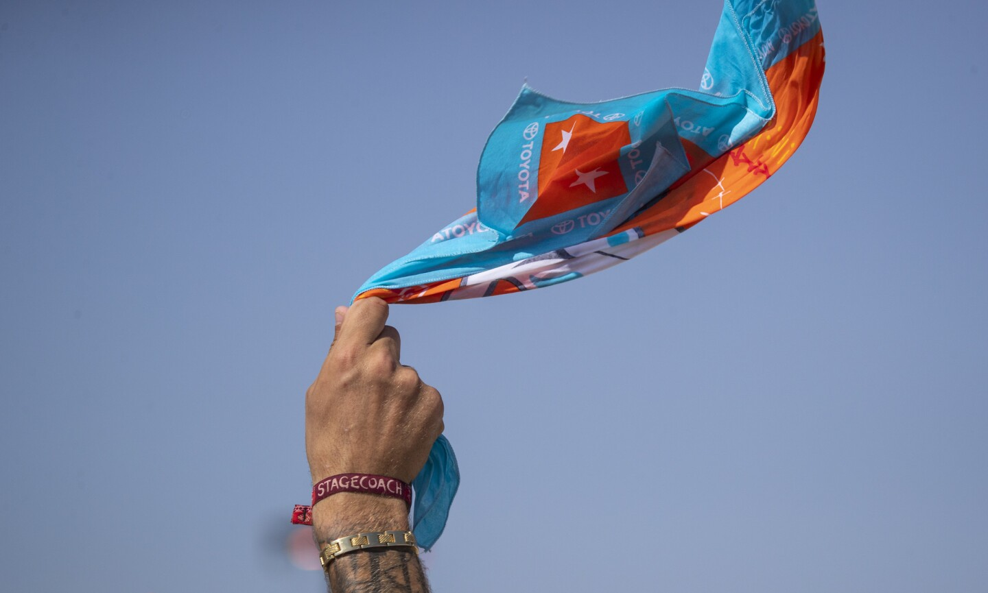 A fan waves a Stagecoach bandana while listening to Ashley McBryde perform Sunday.