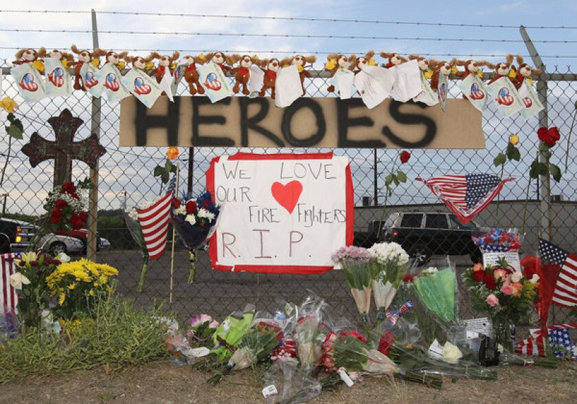 """A makeshift memorial and a sign reading """"Heroes"""" is displayed outside of Station 7 in Prescott, Ariz., which housed the Granite Mountain Interagency Hotshot Crew."""