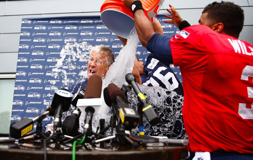 Pete Carroll gets it: The Seattle Seahawks coach gets doused by Russell Wilson, right, and Zach Miller as part of the ALS Ice Bucket Challenge.