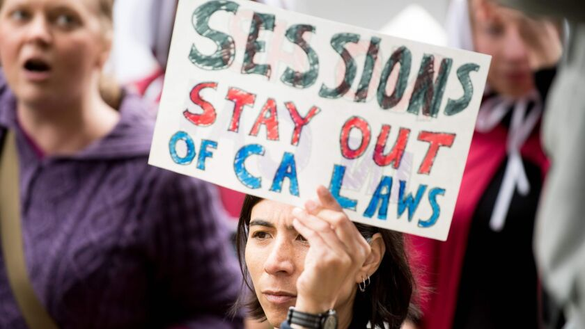People protest outside a speech by U.S. Atty. Gen. Jeff Sessions on Wednesday in Sacramento, where he admonished state politicians for not cooperating with federal authorities on immigration enforcement issues.